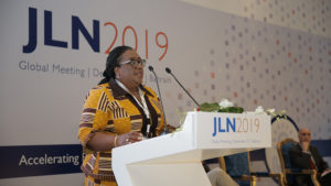 Dr. Lydia Dsane-Selby speaks at a podium on stage at the 2019 JLN Global Meeting.